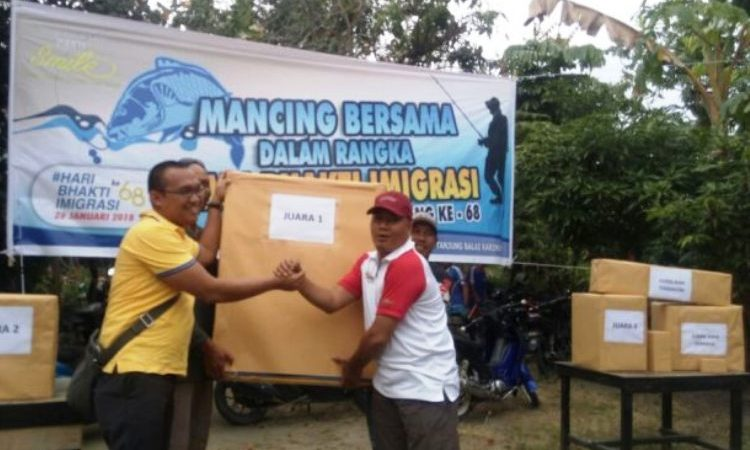 Kepala Kantor Imigrasi Karimun, Mas Arie Yuliansyah (kaos kuning) menyerahkan hadiah kepada juara I mancing bersama